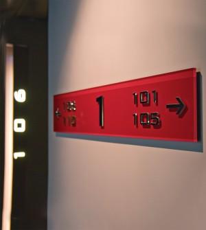 Línea de señalización en plexiglas de color, con letras de metal en relieve