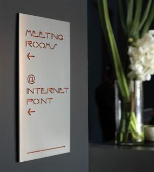 Línea de señalización de metal con caracteres estarcidos y soporte de plexiglas